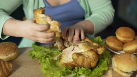 greedily : Overweight woman tearing pieces of meat off roast chicken, eating them greedily