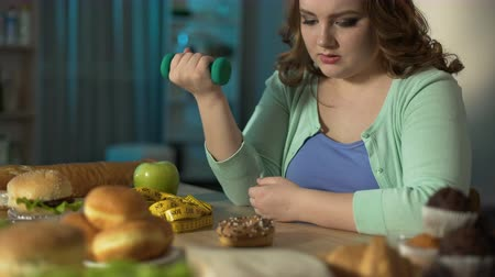 refusal to eat : Lady sitting at table, flexing arm with dumbbell in hand, hungry eyes on donut