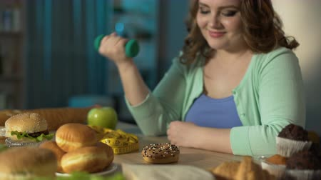 victorious : Overweight girl lifting small dumbbell and looking at donut with smirk, diet Stock Footage