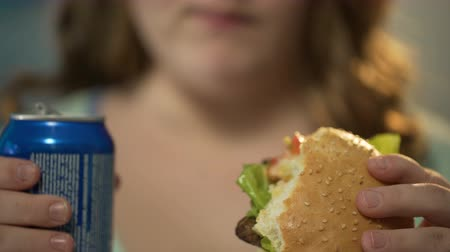 diety : Girl eating fatty burger and drinking sugary soda from can, overeating junk food