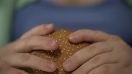 hambúrguer : Female teenager biting big burger, fast food overeating problem, hands close-up Vídeos