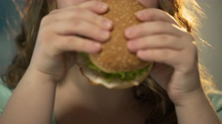 étkezik : Fat girl holding fast food burger with both hands and chewing it, face closeup Stock mozgókép