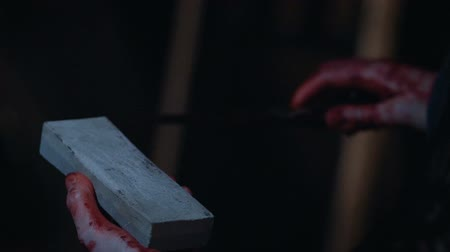 bloody hands : Bloody killer sharpening knife, psychopath preparing for crime, slow-motion