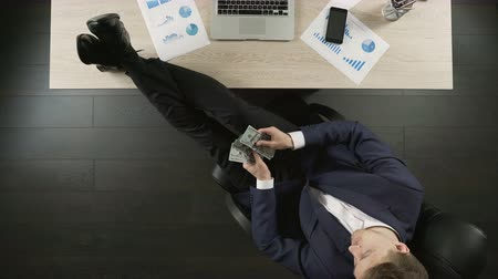 rentável : Relaxed wealthy businessman counting money, sitting with feet on table, top view