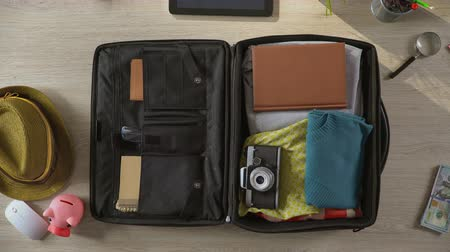 dava : Animated things quickly filling suitcase, bag leaving room, top view stop-motion