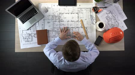 designing : Engineer nervously checking drawings before beginning of building construction Stock Footage