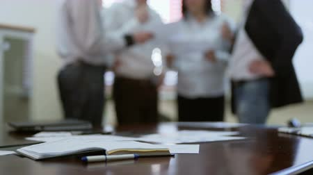 devise : Employee joining colleagues in group discussion over report papers in a meeting