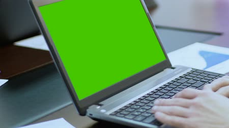 görgetés : Person working on laptop with green screen, using touchpad, scrolling web pages