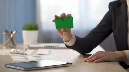 id : Businesswoman showing business card with green field, banking services ad