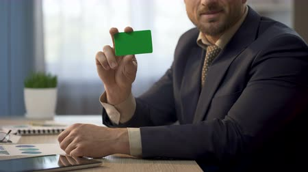 financiamento : Employee sitting at office desk, showing card in green color, insurance plan