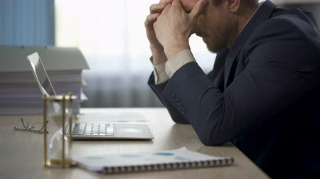 lifeless : Company worker sitting at office desk, rubbing temples, tiredness, overtime work