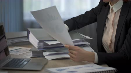 vyčerpání : Woman overloaded with paperwork putting head on folders pile, working long hours