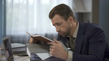 vyčerpání : Exhausted businessman looking at long list in notebook and putting it on head