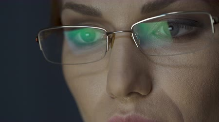 transmitting : Laptop screen reflected in glasses, female working on laptop, concentration