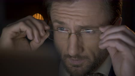 költő : Man putting on glasses, looking at laptop, screen reflected in glasses, thinking Stock mozgókép