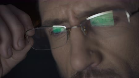 evidência : Laptop screen with files reflected in glasses, detective working at night