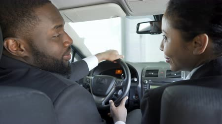 corporate affairs : Two multi-ethnic colleagues flirting, discussing business in car, having affair