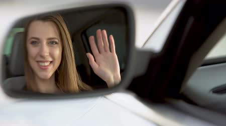 cheerfulness : Female celebrity sitting in vehicle and waving hand, rearview mirror reflection Stock Footage