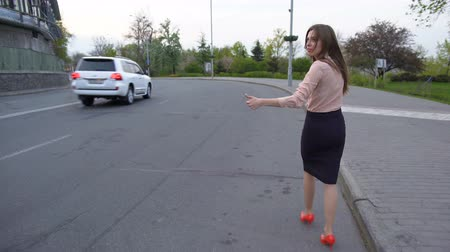 stopping : Young beautiful business lady walking on the road and trying to hitch a car