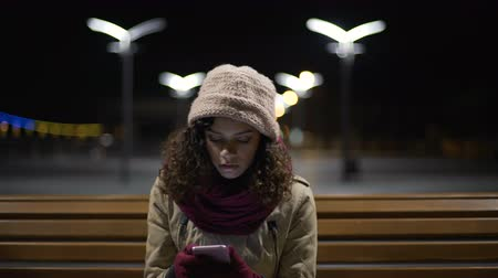 curly haired : Cute lady reading e-mail on her smartphone and becoming upset and disappointed