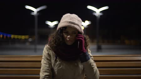 curly haired : Unhappy frozen girl sitting outdoors, cannot reach guy by phone, failed date Stock Footage