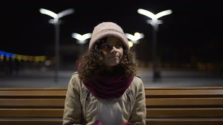 curly haired : Beautiful girl sitting alone at night bus station, browsing schedule on gadget Stock Footage
