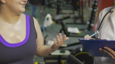 weight training : Obese girl exercising on treadmill in gym, talking to nurse aside, weight watch Stock Footage