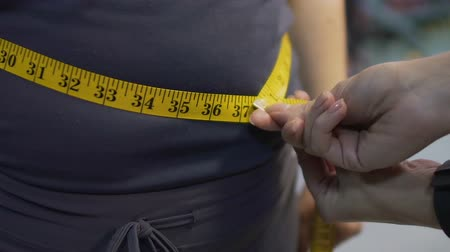 palce : Obese female getting her waist measured with tapeline, results of weight loss