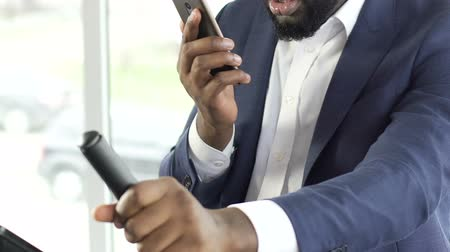 sebesség : Black man wearing business suit exercising on stationary bike, talking on phone Stock mozgókép