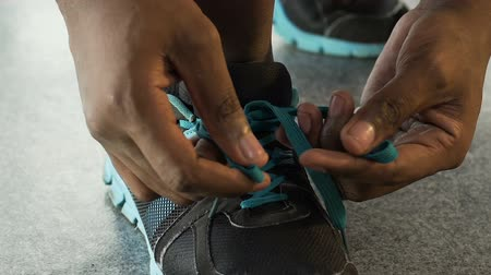 tornacipő : Multiracial guy tying up shoelaces and leaving, basketball player, close-up Stock mozgókép