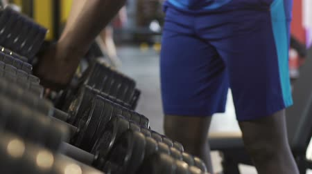 enduring : Males taking heavy dumbbells from stand in gym, physical workout, weight lifting