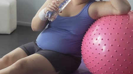 hydratace : Fat young lady sitting on floor drinking water, leaning on fitness ball, workout