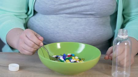 lucrative : Girl taking spoon to eat tablets from bowl, slow motion, pharmaceutical products