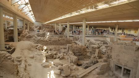 извержение : People visiting ongoing ancient Akrotiri settlement excavation site on Santorini