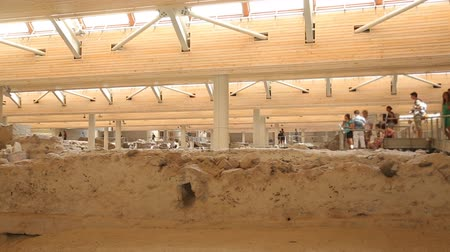 millennium : Tourists viewing remains of ancient settlement of Akrotiri, Greece from walkways Stock Footage