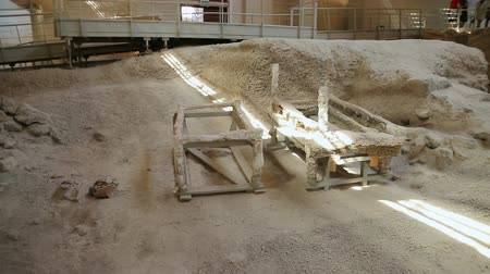 starožitnosti : Frames of ancient table-like constructions standing on excavation site, Akrotiri