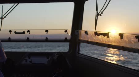 моряк : Experienced old captain standing at dashboard, steering his vessel into open sea