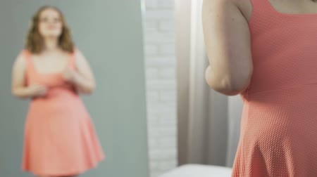 esteem : Young overweight woman standing in front of mirror, satisfied with reflection