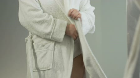 дополнительный : Chubby woman closing bathing robe, unhappy with her body reflection in mirror