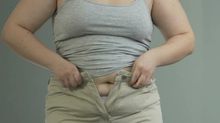 nézett : Fat lady putting efforts to button and zip her pants, weight problems, dieting Stock mozgókép