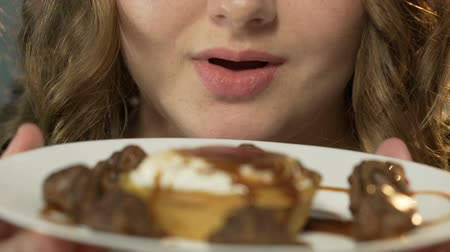 водянистый : Girl licking lips at sweets, chocolates under caramel topping on plate, closeup