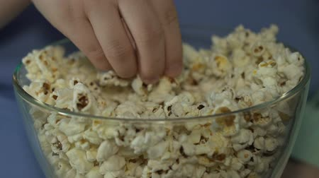 pop corn : Adolescente che mangia velocemente popcorn dalla ciotola in cinema assorto dal film, primo piano Filmati Stock