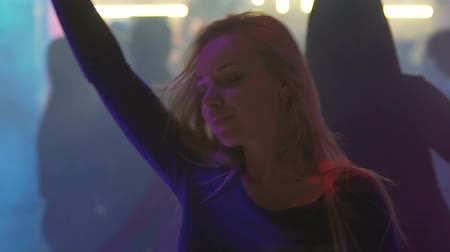eufória : Pretty blonde woman smiling, dancing and enjoying atmosphere at nightclub party Stock mozgókép