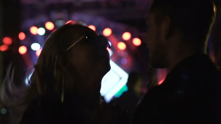 зависать : Young woman dancing with boyfriend and shaking hands at rock festival, relax