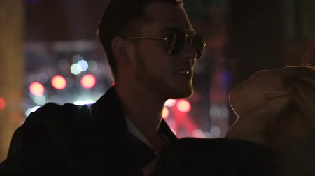 párok : Attractive man in sunglasses dancing with blonde woman at night club, slowmotion