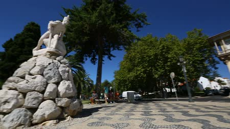 comemoração : City square with monument to soldier, people having rest in shadow, panorama