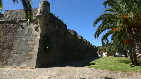 fortifying : Old high fortifying wall in city with sidewalk along it, panorama and sequence