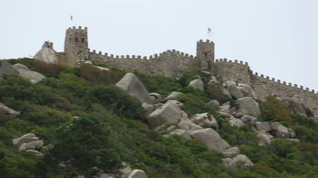 fortifying : Stone fortifying wall shown from foot of steep hill, boulders scattered on slope Stock Footage