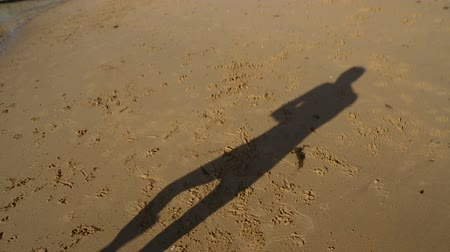 charged : Happy man dancing funny dance on beach with his shadow casted on sand, good mood