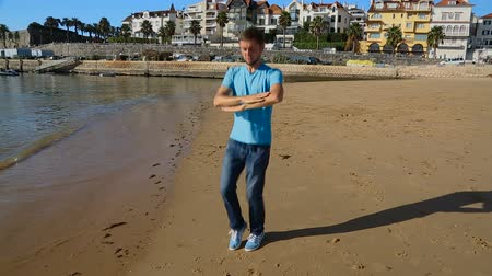 charged : Funny guy dancing Ukrainian national dance on sea coast, shadow moving on sand